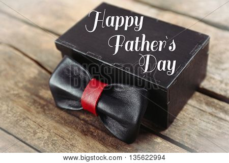 Happy father's day concept. Black and red leather bow tie and gift box on wooden table, close up