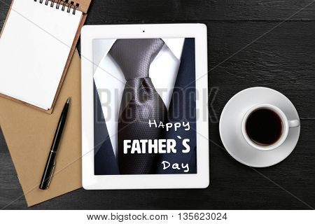 Happy father's day concept. Digital tablet with cup of coffee and notebook on wooden table, closeup