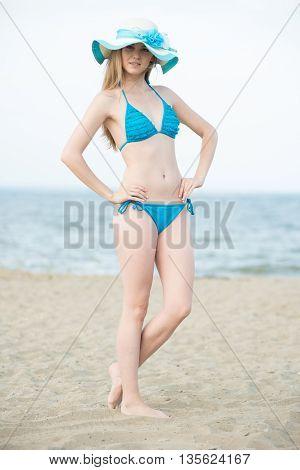 Young lady sunbathing on a beach. Beautiful woman posing at the summer sand beach. Outdoor summer portrait of pretty sport style woman in blue bikini. Ocean sea coast. Beautiful fit tan girl. Sexy slim model caucasian ethnicity outdoors.