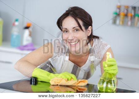 woman in green protective gloves cleaning induction cooker with sponge.