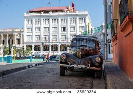 Santiago de Cuba Cuba - January 10 2016: Typical scene of one of streets in the center of Santiago de cuba - Colorful architecture people walking around. Town square old vintage american car. Santiago is the 2nd largest city in Cuba