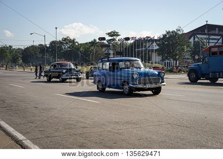 Santiago de Cuba Cuba - January 11 2016: Typical scene of one of streets in the center of Santiago de cuba -people walking around and vintage american cars on the roads. Santiago is the 2nd largest city in Cuba