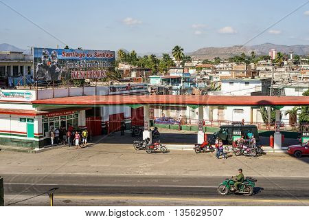 Santiago de Cuba Cuba - January 11 2016: Typical scene of one of streets in the center of Santiago de cuba - Petrol stations where city residents can refuel their old American motorcycles and cars up. Over the tank is a poster with Raul Castro. Santiago i