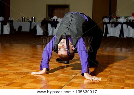 A young boy does a backbend on the dance floor at a wedding reception.