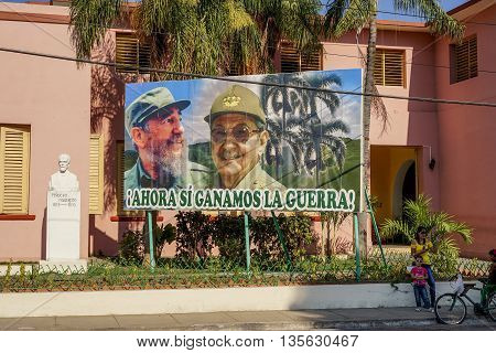 Santiago de Cuba Cuba - January 12 2016: Typical scene of one of streets in the center of Santiago de cuba - Big poster of Raul and Fidel Castro. people walking around. Santiago is the 2nd largest city in Cuba