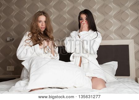 Beautiful sexy two girls having fun in bedroom, pillow fight. Blonde woman and brunette lady smiling, looking at camera.