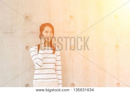 Woman pick up a call with copyspace on wall