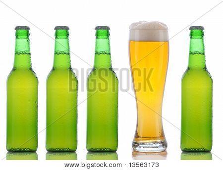 Four Green Beer Bottles And Full Glass