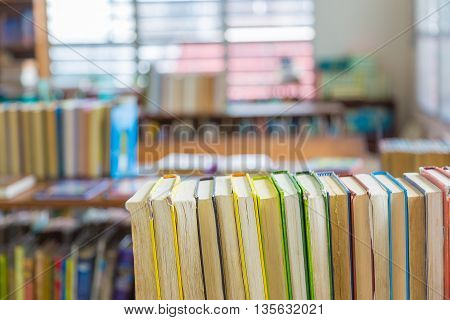 Hard covered library books line up on a shelf selective focus with blurred background