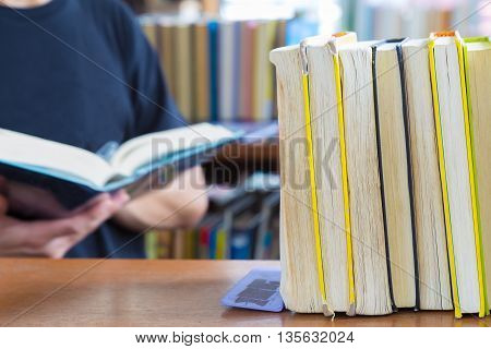 Hard covered library books line up on a shelf selective focus with blurred man holding reading a book background