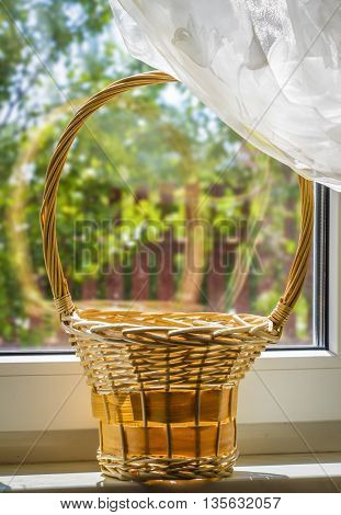Wooden wicker basket standing on a windowsill on a clear summer day