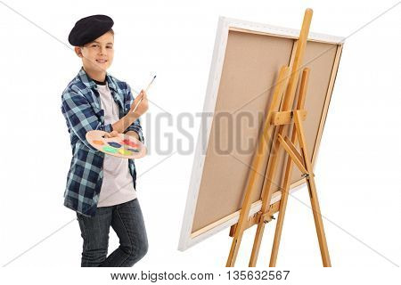Artistic kid holding paintbrush and a color palette next to a canvas isolated on white background