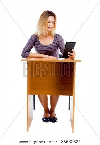 back view of woman sits by the table and looks at the screen of the tablet.  Rear view people collection.  backside view of person.  I front view of a girl behind office desk reading an e-book.