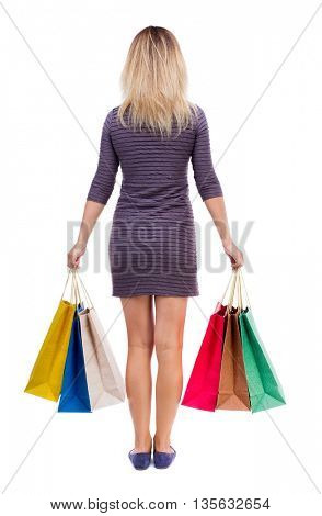 back view of woman with shopping bags . backside view of person.  Rear view people collection. Isolated over white background. Girl in a short dress is holding in both hands paper bags.