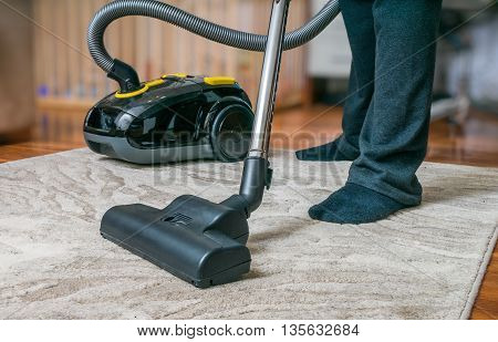 Man Is Cleaning Carpet With Vacuum Cleaner.