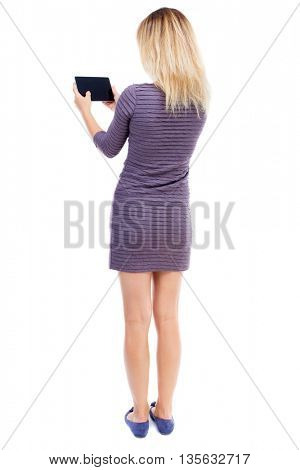 back view of standing young beautiful  girl with tablet computer in the hands of.  backside view of person.  Isolated over white background. A girl in a short dress stands back and read e-books.