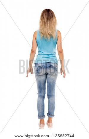 back view of standing young beautiful  woman.  girl  watching. Rear view people collection.  .  Isolated over white background. The girl in jeans and a blue t-shirt standing with her hands.