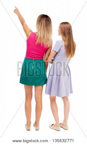 Back view of two pointing young girl. Rear view people collection.  backside view of person. A couple of girls in dresses worth considering something in the sky.