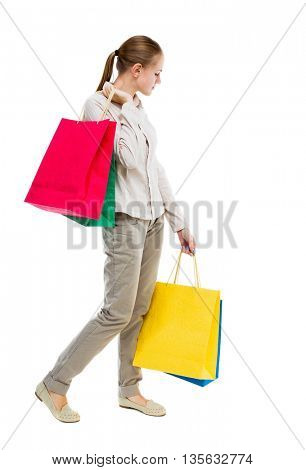 back view of woman with shopping bags . beautiful brunette girl in motion.  backside view of person.  Rear view people collection Girl in gray jeans goes to the left and carries paper bags.