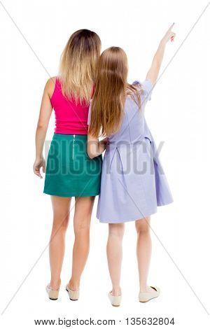 Back view of two pointing young girl. Rear view people collection.  backside view of person. Rear view. Isolated over white background. Two girlfriends standing together and showing his hand up.