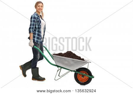 Full length portrait of a young woman pushing a wheelbarrow full of dirt isolated on white background
