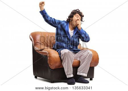 Studio shot of a sleepy guy yawning seated on an armchair isolated on white background