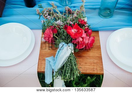 Bridal Bouquet Of Wild Flowers On A Wedding Table