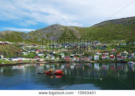 Green Hill With Fishing Town On The Side Of Fjord, Mageroya.