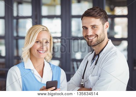 Portrait of smiling doctors using mobile phone while standing in hospital