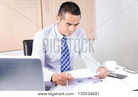 Asian business man looking at document in work place office