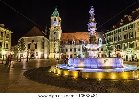 BRATISLAVA SLOVAKIA - 29th April 2016: Old Town Hall in Bratislava Slovakia at night with part of Maximilians Fountain in the foreground. People can be seen.