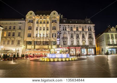 BRATISLAVA SLOVAKIA - 29TH APRIL 2016: A view of buildings and Maximilian's Fountain in Old Town Bratislava at night. People and the outside of restaurants can be seen.