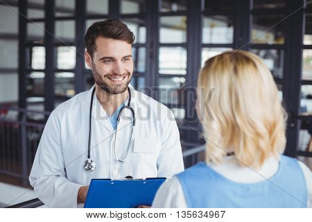 Smiling doctors discussing while standing at hospital