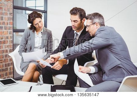 Business people holding documents while discussing at office