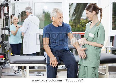 Nurse Putting Crepe Bandage On Senior Man's Hand