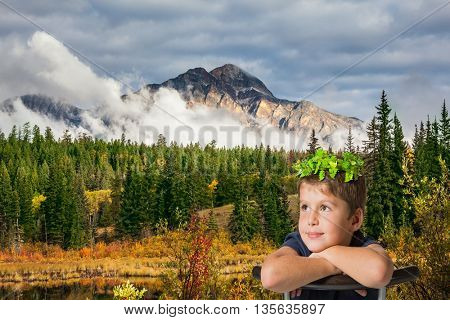 Jasper National Park in the Rocky Mountains of Canada. The yellow and orange autumn grass and trees. Picturesque mountains and clouds. Handsome boy with bright eyes sitting