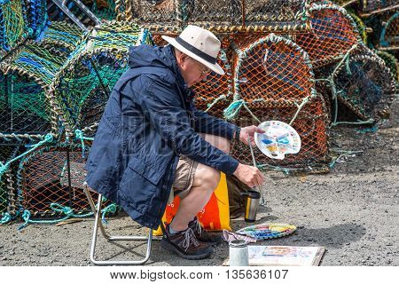 Crail Scotland - July 26 2012: Fife area a painter in the harbor.