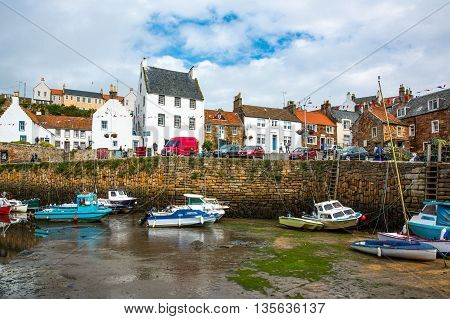 Crail Scotland - July 26 2012: Fife area fishing boats and yachts in the harbor at low tide.