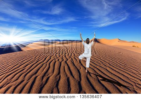 Yoga in the desert. A middle-aged woman in a white performs asana