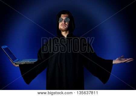 A hacker hiding his face behind glasses and a hood typing on his laptop. Programmer.