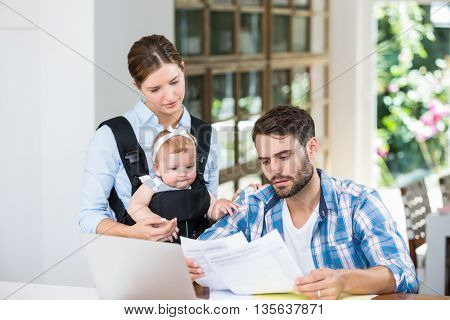 Man and woman with baby reading documents by table at home