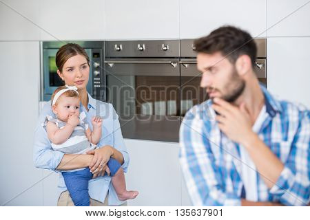 Woman with baby looking at tensed husband standing in foreground