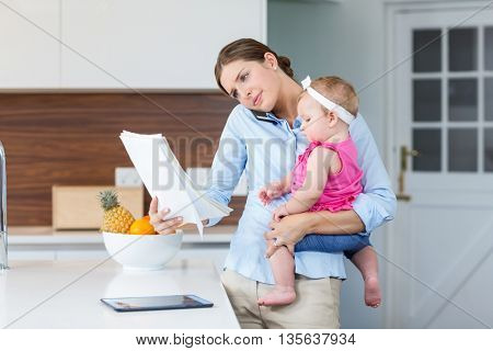 Woman reading documents while carrying baby girl by table at home