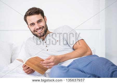 Portrair of smiling man holding book on bed at home