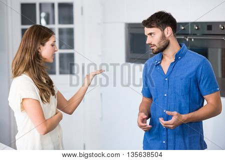 Young couple arguing in kitchen at home