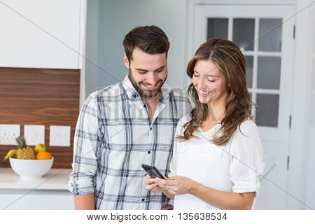 Happy couple looking in mobile phone while standing at home