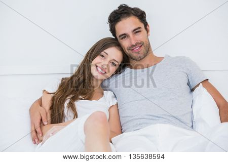 Portrait of happy couple sitting on bed at home