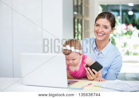 Happy woman holding mobile phone while sitting with baby girl at home