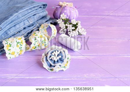 Blue flower brooch made of old jeans, lace and artificial stamens. Summer pretty denim brooch. Recycling Fashion. Jeans, pincushion, thread, needles, pins, lace on lilac wooden background