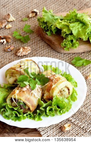 Fried zucchini stuffed with cheese, walnuts and herbs. Homemade zucchini appetizer arranged on lettuce and a plate. Fresh green lettuce on a wooden board. Healthy and delicious summer food